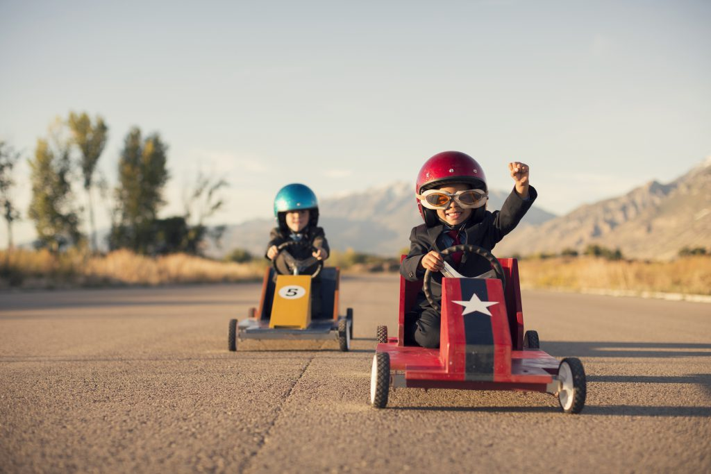 A young boy dressed as a businessman raises his arm in success as his homemade box car is in first place. Both boys are wearing helmets and goggles.